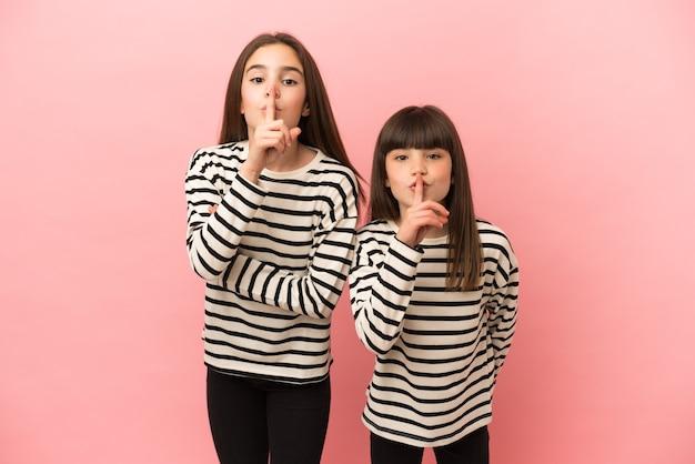 Petites sœurs filles isolées sur fond rose montrant un signe de silence geste mettant le doigt dans la bouche