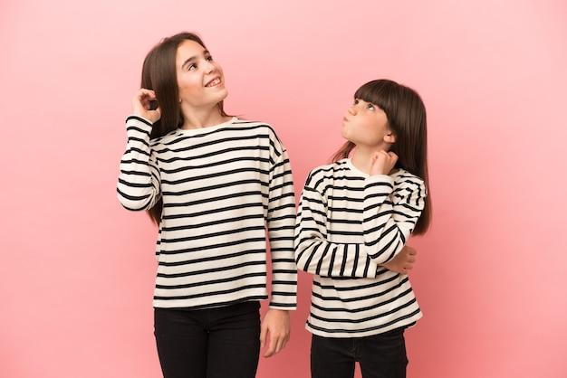 Petites soeurs filles isolées sur fond rose pensant à une idée en se grattant la tête