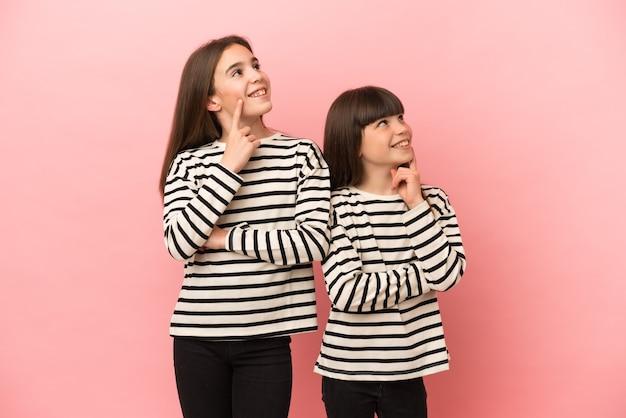 Petites sœurs filles isolées sur fond rose pensant à une idée tout en levant les yeux
