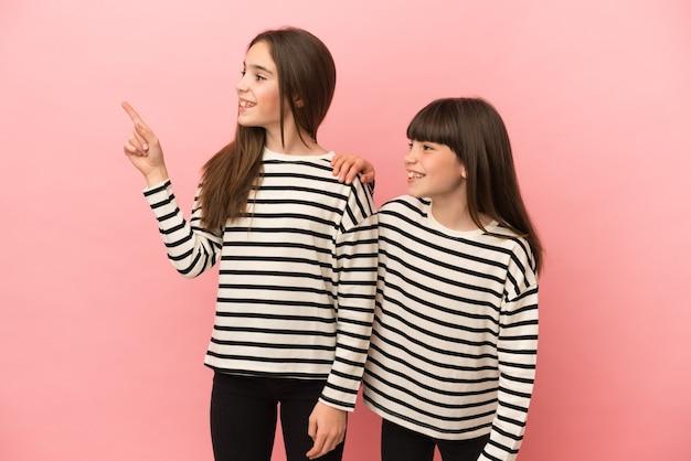 Petites sœurs filles isolées sur fond rose pointant vers le côté pour présenter un produit