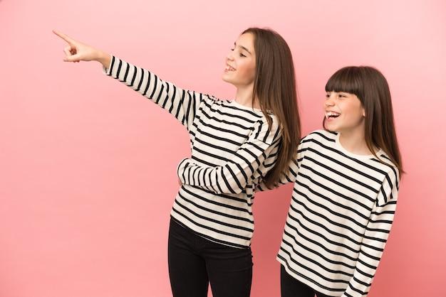 Petites sœurs filles isolées sur fond rose présentant une idée tout en souriant vers