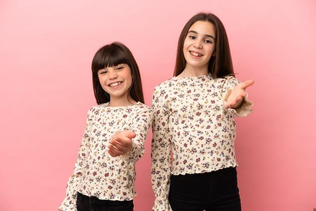 Petites sœurs filles isolées sur fond rose se serrant la main pour conclure une bonne affaire
