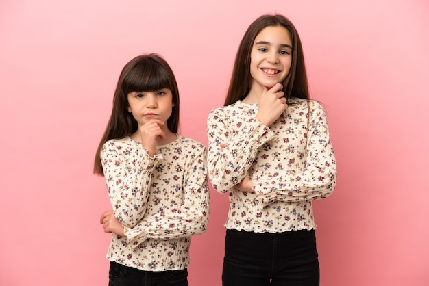 Petites soeurs filles isolées sur fond rose souriant et regardant vers l'avant avec un visage confiant