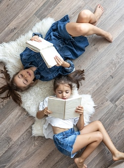 Les petites sœurs des filles lisent des livres allongés sur le sol, vue de dessus.