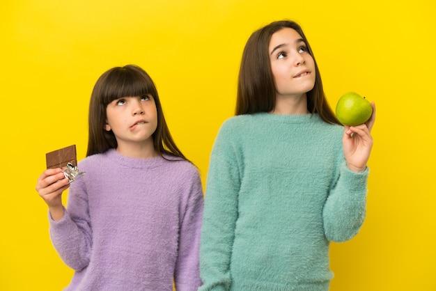 Petites soeurs isolées sur fond jaune ayant des doutes en prenant une tablette de chocolat dans une main et une pomme dans l'autre