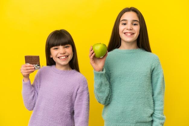Petites sœurs isolées sur fond jaune prenant une tablette de chocolat dans une main et une pomme dans l'autre