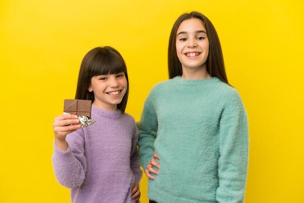 Petites sœurs isolées sur fond jaune prenant une tablette de chocolat et heureux