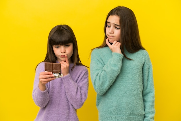 Petites soeurs isolées prenant une tablette de chocolat et ayant des doutes