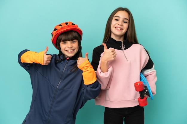 Petites sœurs pratiquant le cyclisme et patineur isolé sur fond bleu donnant un geste de pouce en l'air avec les deux mains et souriant