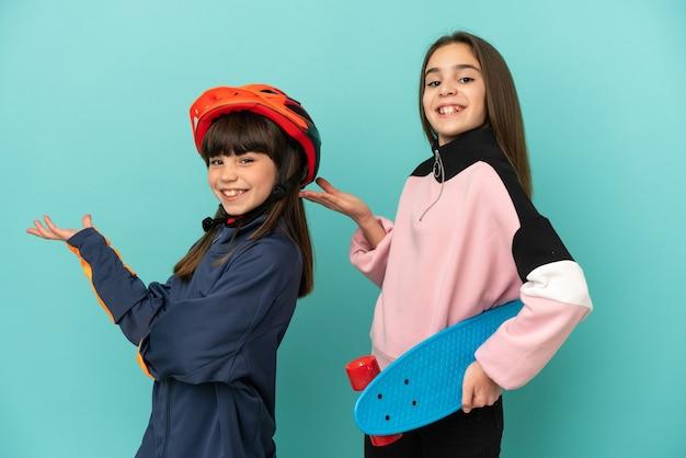 Petites sœurs pratiquant le cyclisme et patineur isolé sur fond bleu étendant les mains sur le côté pour inviter à venir
