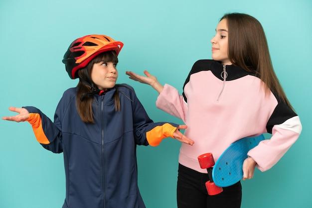 Petites sœurs pratiquant le cyclisme et patineur isolé sur fond bleu faisant un geste sans importance tout en soulevant les épaules