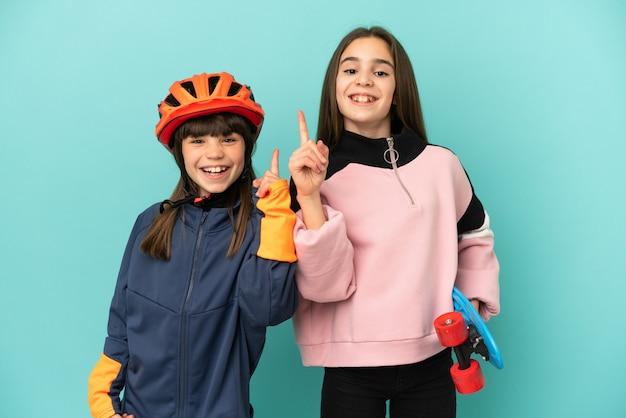 Petites sœurs pratiquant le cyclisme et patineur isolé sur fond bleu montrant et levant un doigt en signe du meilleur