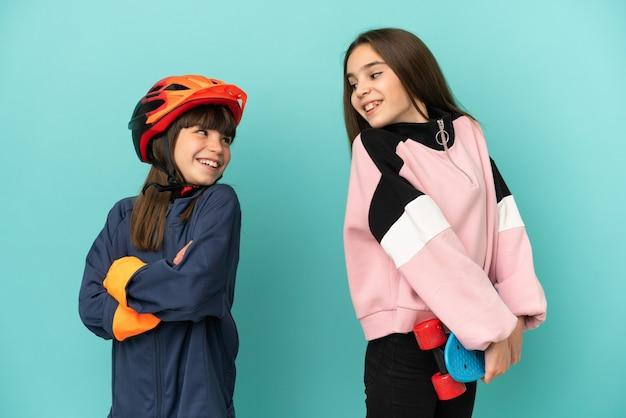 Petites sœurs pratiquant le cyclisme et patineur isolé sur fond bleu regardant par-dessus l'épaule avec un sourire