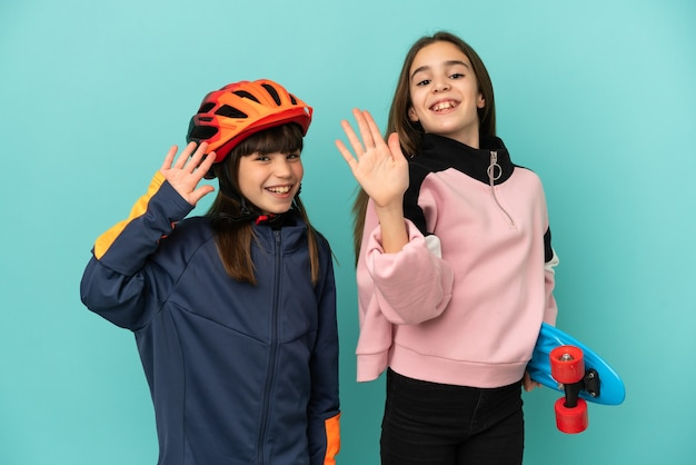 Petites sœurs pratiquant le cyclisme et patineur isolé sur fond bleu saluant avec la main avec une expression heureuse