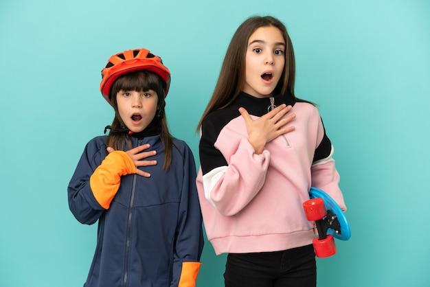 Petites sœurs pratiquant le cyclisme et patineur isolé sur fond bleu surpris et choqué tout en regardant à droite