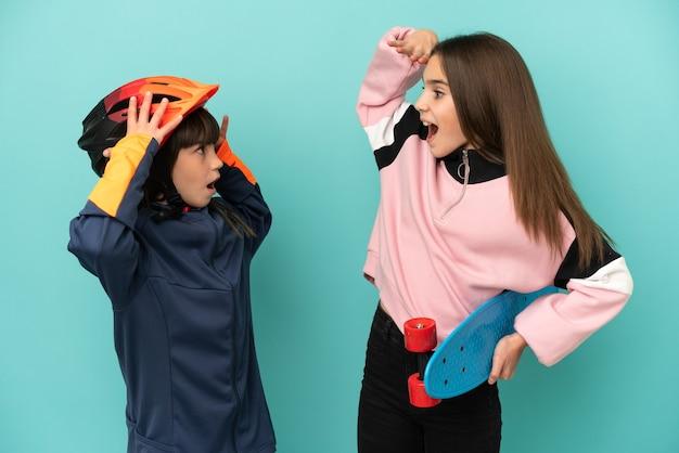 Petites sœurs pratiquant le cyclisme et patineur isolé sur fond bleu avec surprise et expression faciale choquée