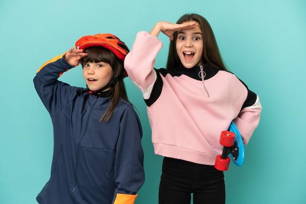 Les petites sœurs pratiquant le cyclisme et le patineur isolé sur fond bleu vient de réaliser quelque chose et a l'intention de la solution