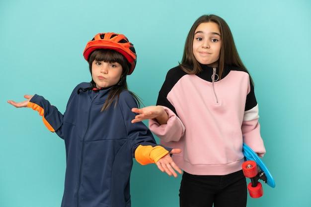 Petites soeurs pratiquant le cyclisme et le patineur isolés sur fond bleu ayant des doutes tout en levant les mains et les épaules