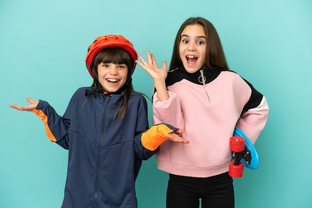 Petites soeurs pratiquant le cyclisme et le patineur isolés sur fond bleu avec une expression faciale surprise et choquée