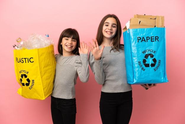 Petites soeurs recyclant le papier et le plastique isolés sur fond rose saluant avec la main avec une expression heureuse
