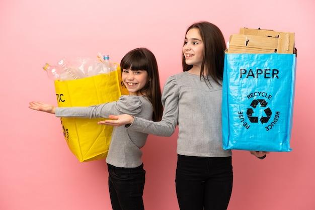 Petites soeurs recyclant le papier et le plastique isolés pointant vers l'arrière et présentant un produit