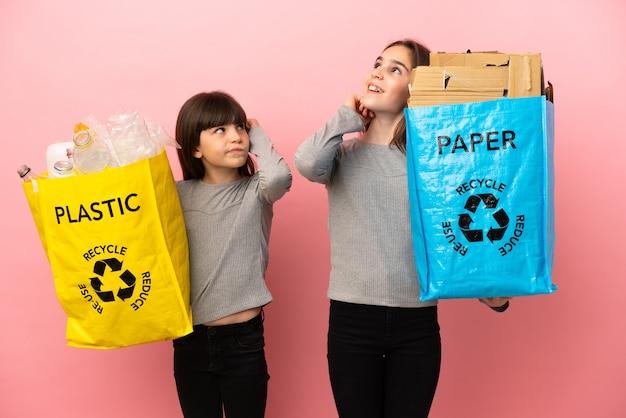 Les petites sœurs recyclent le papier et le plastique isolés en pensant à une idée en se grattant la tête