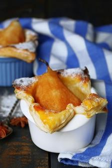 Petites tartes aux poires dans des tasses, sur table en bois