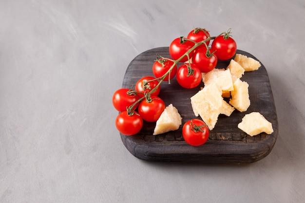 Petites tomates cerises rouges et tranches de fromage sur une vieille planche de bois, gros plan.