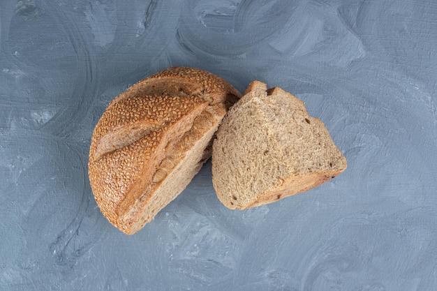 Petites tranches de pain couvert de sésame sur table en marbre.