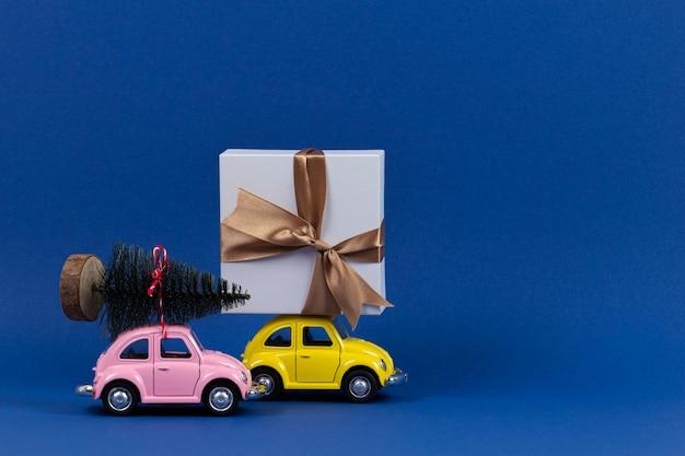 Petites voitures de modèle jouet rétro avec boîte-cadeau et petit arbre de noël sur bleu marine