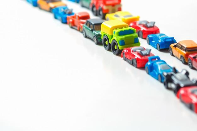 Les petites voitures en plastique multicolores s'alignent sur du blanc