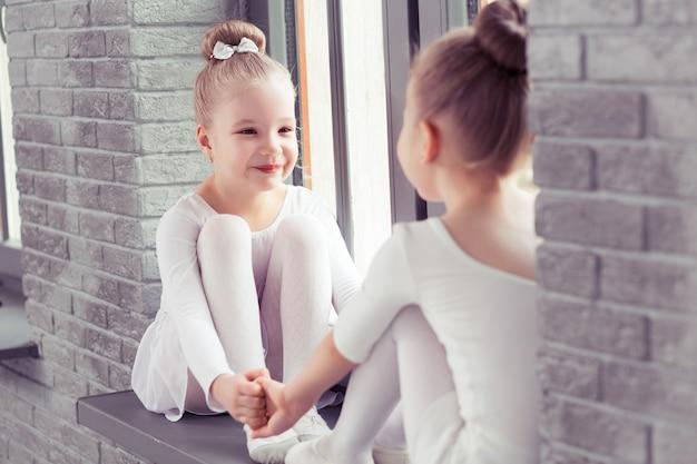 Petits amis enfants dansant le ballet assis sur le rebord de la fenêtre et embrassant tout en souriant ensemble