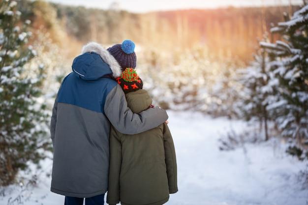 Petits amis garçons s'embrassent dans la forêt d'hiver enneigée