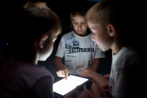 Petits amis partageant une tablette pour s'amuser