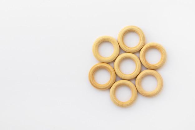 Petits anneaux en bois sur fond blanc. anneau de dentition pour bébé en bois naturel. jouet pour enfants respectueux de l'environnement. vue de dessus, mise à plat avec espace de copie.