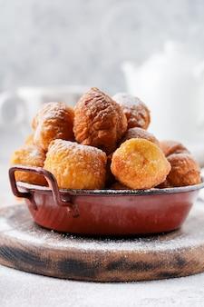 Petits beignets. biscuits frits au lait caillé maison en graisse profonde et saupoudrés de sucre glace dans une assiette vintage