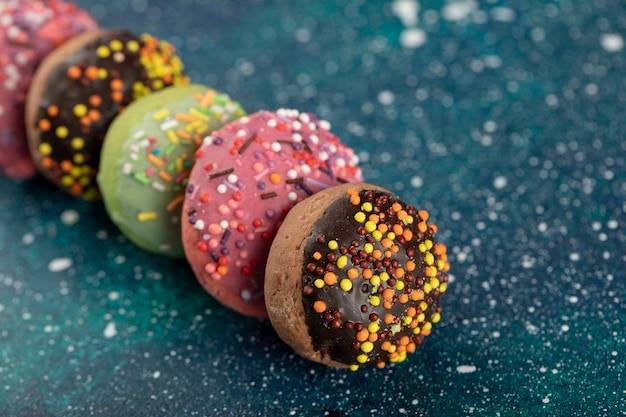 Petits beignets colorés avec des pépites sur une surface bleue.