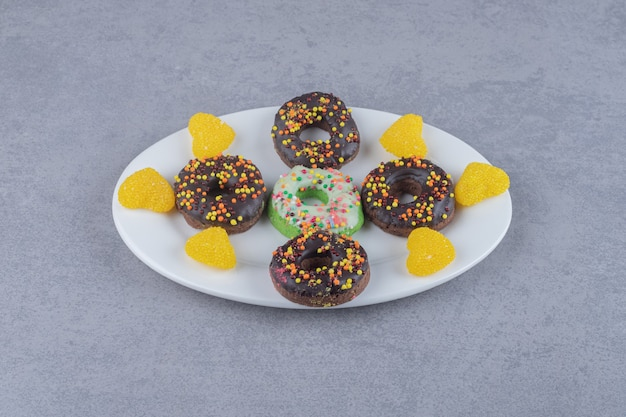 Petits beignets et marmelades soigneusement disposés sur un plateau sur une surface en marbre