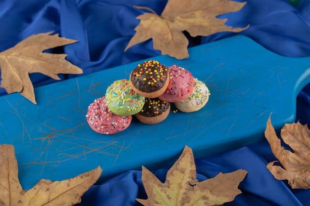 Petits beignets sucrés colorés sur une planche de bois bleue.