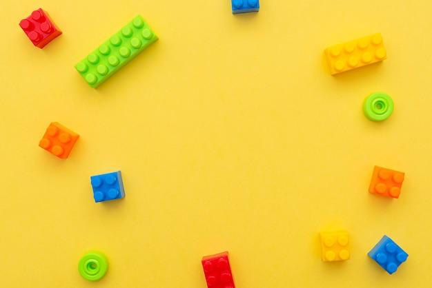 Petits blocs de constructeur en plastique sur fond jaune, mise à plat, vue de dessus, espace pour le texte