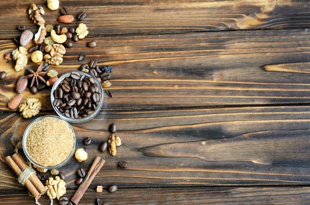 Petits bols en verre contenant du sucre brun de canne et des grains de café avec des ingrédients sains comme des raisins secs, des noix et de la cannelle sur du bois naturel avec fond