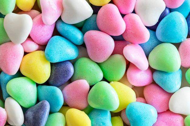 Petits bonbons colorés divers en forme de coeur, fond, gros plan