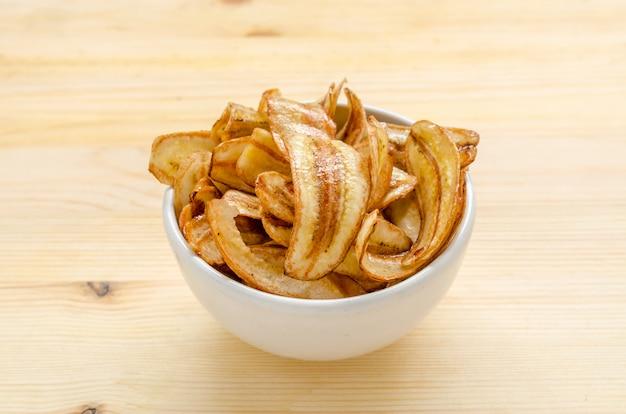 Petits chips de banane sur une table en bois