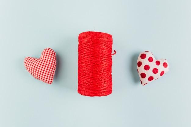 Petits coeurs doux et brillants avec un rouleau de corde sur la table