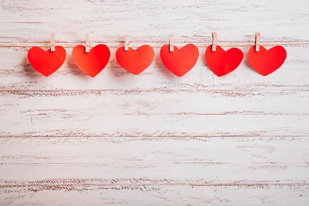 Petits cœurs en papier épinglés à une corde sur un mur