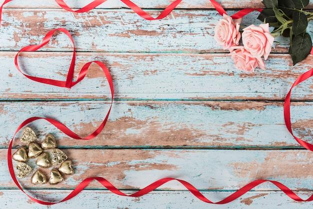 Petits coeurs avec des roses roses sur la table