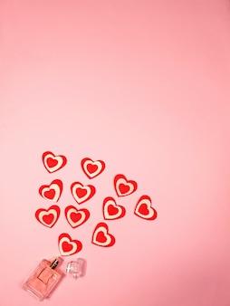 Petits coeurs rouges et une bouteille de parfum sur une rose