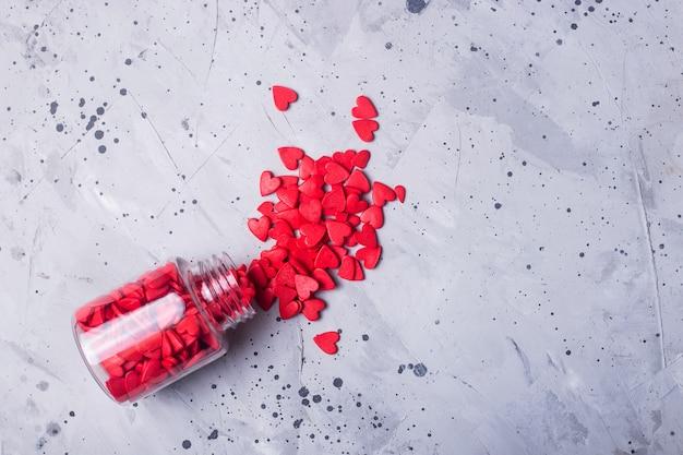 Petits coeurs rouges sur une table grise comme symbole de l'amour le jour de la saint-valentin