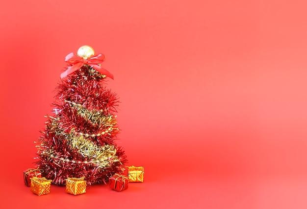 Petits coffrets cadeaux et arbre de noël en guirlande décorative brillante et lumineuse sur fond rouge.
