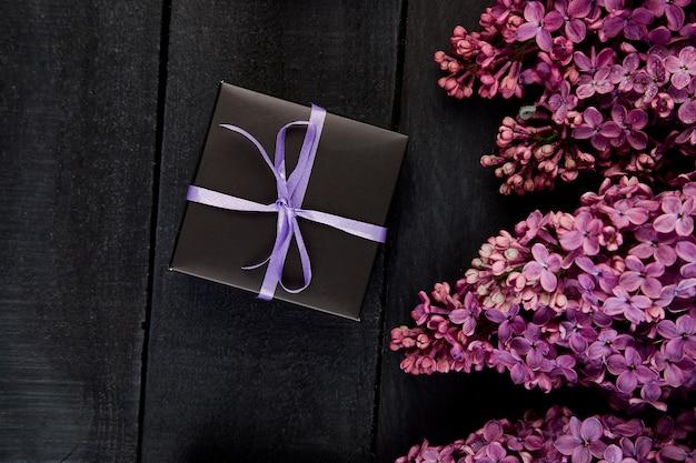 Petits coffrets cadeaux noirs enveloppés de ruban violet avec du lilas naturel.